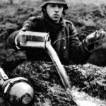 A German soldier, with Panzerfaust beside him, bails out his foxhole
